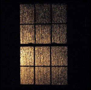 12 paned window; lit up at night by lightning; rain streaming down the panes