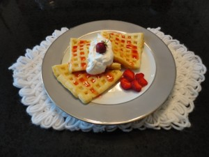 Waffles. strawberry syrup, whipped cream; strawberry garnish, china plate, white yarn place mat
