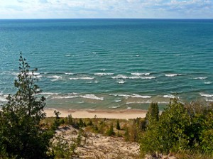 White caps, large lake shore, waves rolling to shore, sandy beach, wooded shore, evergreens, lake horizon,